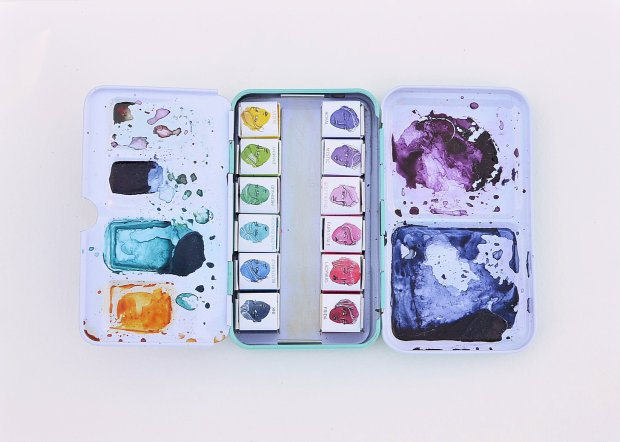 A top view of the open Jane Davenport watercolor tin showing the mixing area and all 12 bright watercolor pans.